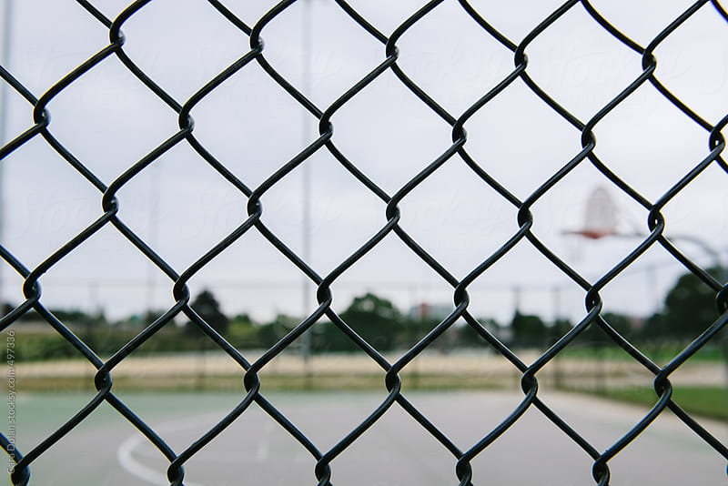 Looking through chain link fence to public basketball court by Cara Dolan for Stocksy United