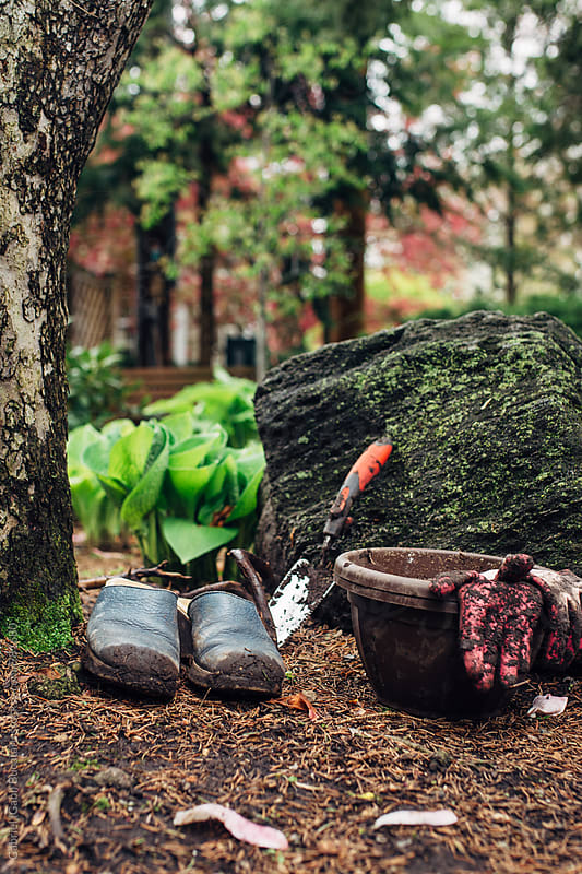 Muddy gardening gloves, shoes and spade by Gabriel (Gabi) Bucataru for Stocksy United
