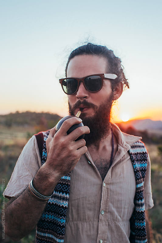 Outdoor Portrait of Bearded Young Man Wearning Sunglasses and Drinking Mate by Julien L. Balmer for Stocksy United