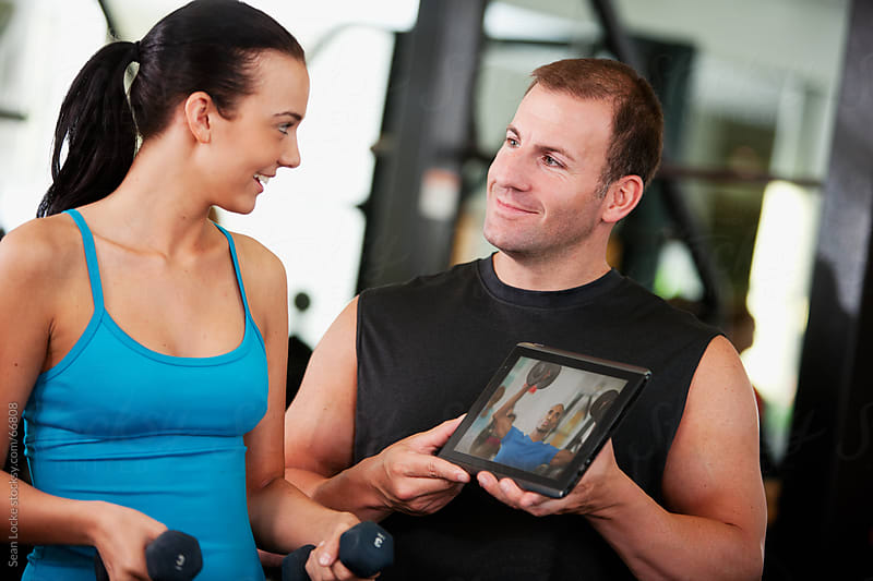 Gym: Trainer Shows Video to Woman by Sean Locke for Stocksy United