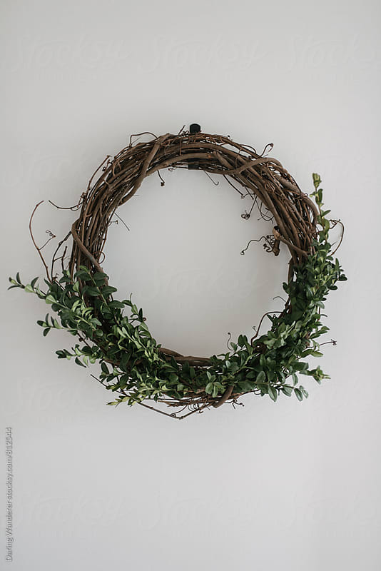Simple diy boxwood holiday Christmas wreath on white wall by Daring Wanderer for Stocksy United