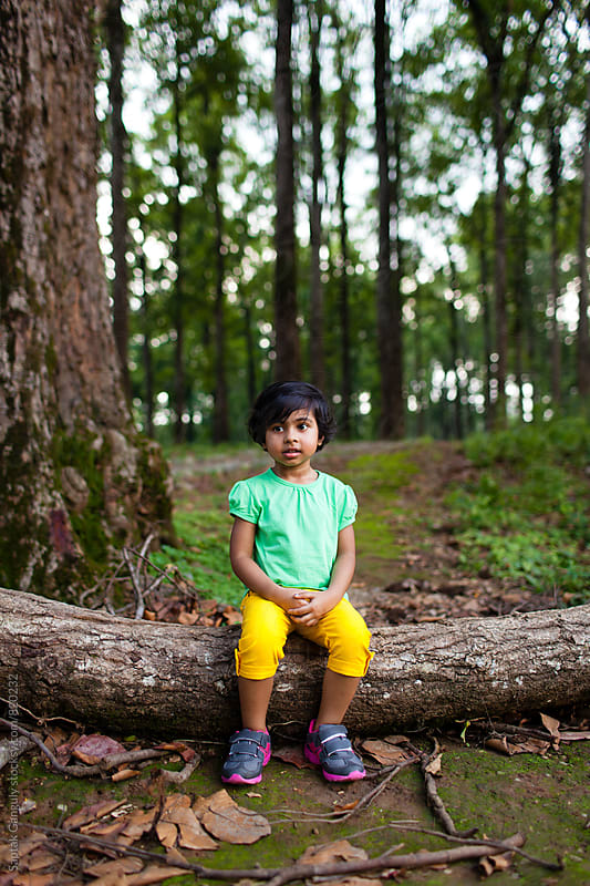 Little girl sitting on a tree trunk in a forest by Saptak Ganguly for Stocksy United