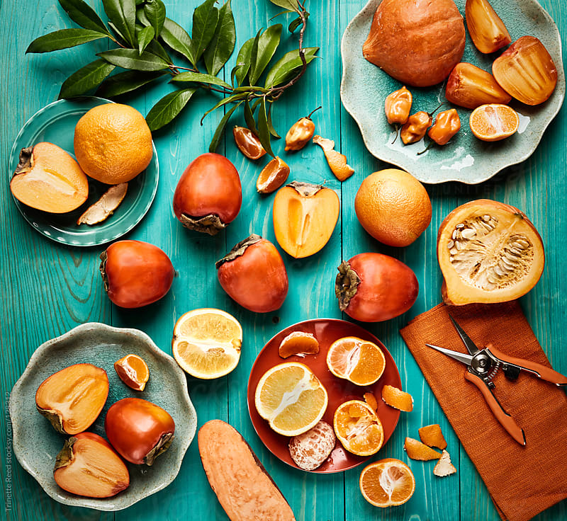 Still life of various orange colored fruits and vegetables on blue wood by Trinette Reed for Stocksy United