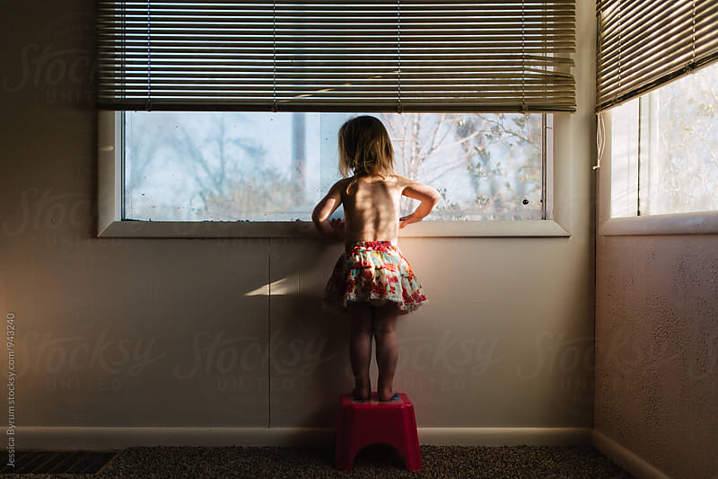 Small child standing on stool looking out of window by Jessica Byrum for Stocksy United