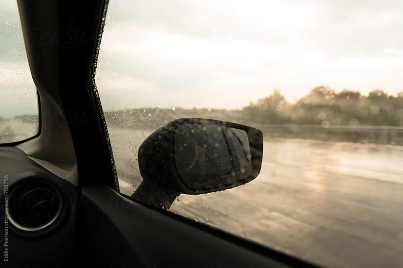 Passenger seat shot of a side view mirror by Eddie Pearson for Stocksy United