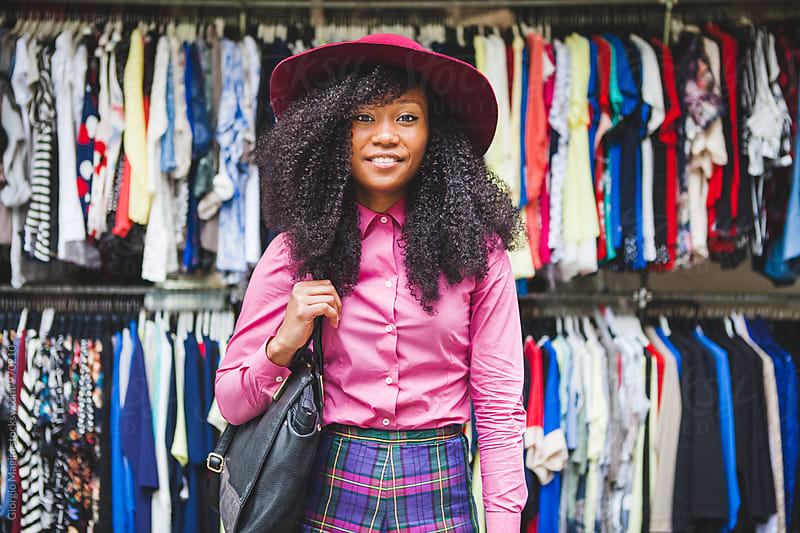 Young Black Woman in front of a Street Marketplace with Clothes by Giorgio Magini for Stocksy United
