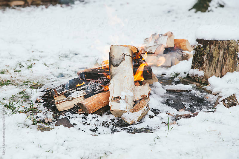 Small wood fire in the snow by Lior + Lone for Stocksy United