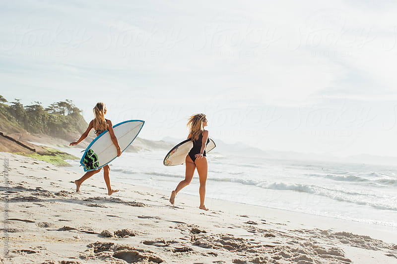 Rio de Janeiro - Two Sexy Female Surfer Girls Running Towards Ocean With Surfboard Under Arm by VISUALSPECTRUM for Stocksy United