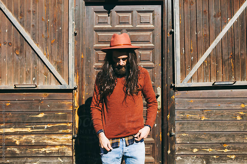 Hipster man standing in front of a wooden cabin in the mountain. by BONNINSTUDIO for Stocksy United