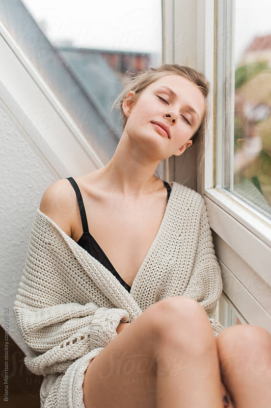 Young Blonde woman sitting in a window relaxing by Briana Morrison for Stocksy United