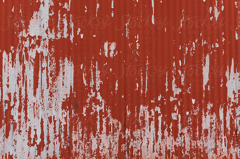 red peeling wall of an old corrugated metal barn by Deirdre Malfatto for Stocksy United