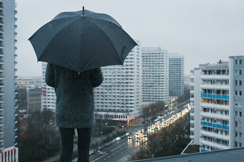 Woman With Black Umbrella Standing on Berlin Rooftop on Rainy Day by Julien L. Balmer for Stocksy United