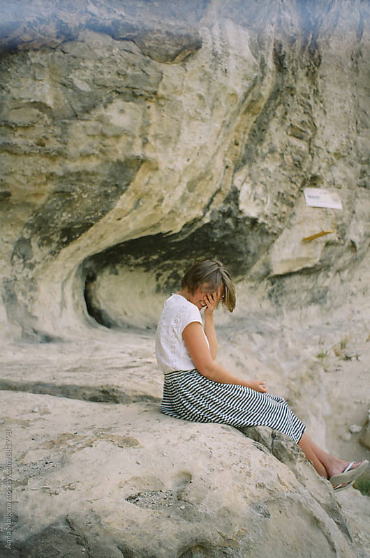 A profile portrait of young smiling blond woman seating on the rock in the mountain by Anna Malgina for Stocksy United