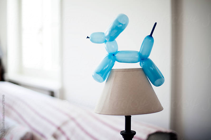 Dog shaped balloon on white lamp in living room by Laura Stolfi for Stocksy United