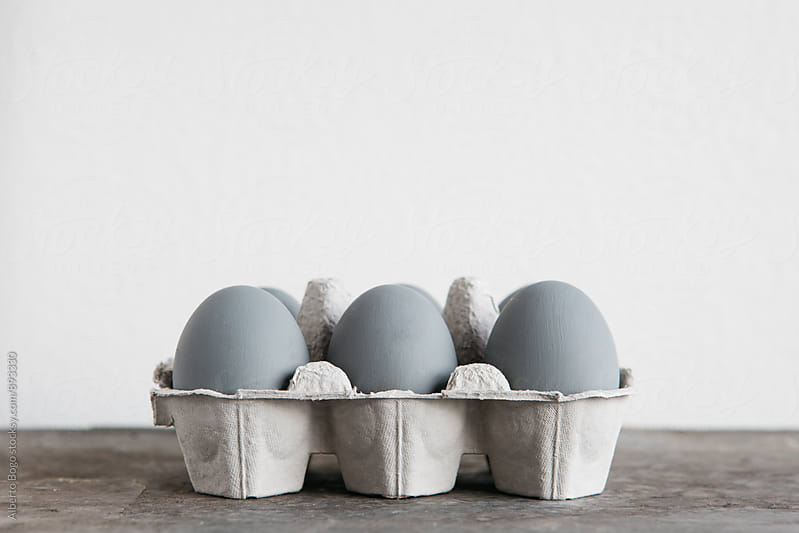 Grey painted eggs in cardboard tray by Alberto Bogo for Stocksy United