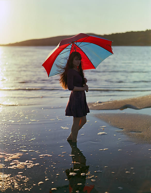 Woman on the beach with a colored umbrella enjoying the sun  by Luca Pierro for Stocksy United