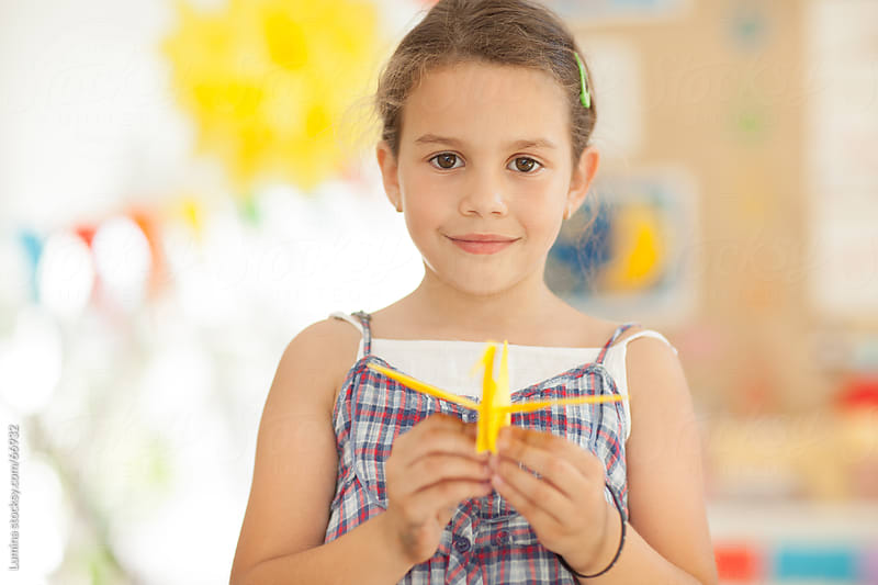 Smiling Girl Holding an Origami Bird by Lumina for Stocksy United