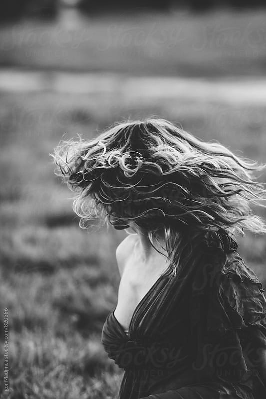 motion, a pretty woman with lush hair in a dress in nature, portrait by Igor Madjinca for Stocksy United