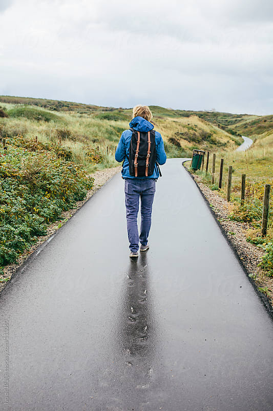 Young man with a backpack walking on a wet road in the middle of by Ivo de Bruijn for Stocksy United