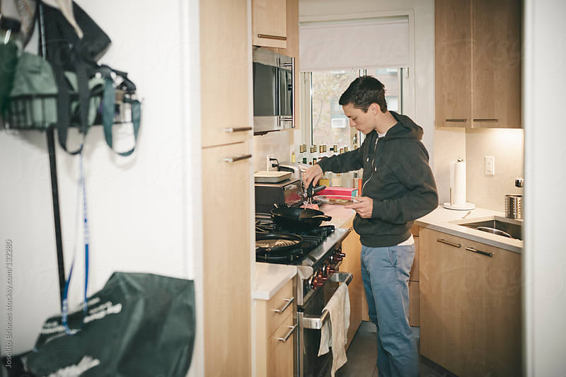 Young Male University Student Makes Egg on Toast as Breakfast in Kitchen by Joselito Briones for Stocksy United