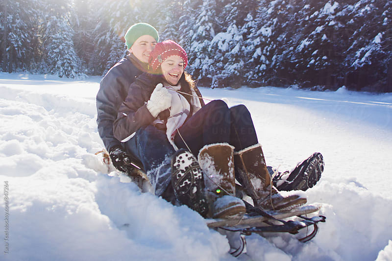 young couple riding sled in deep snow by Tana Teel for Stocksy United