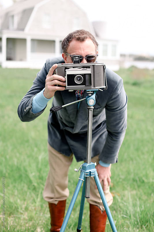 Man with a vintage camera  by Jennifer Brister for Stocksy United