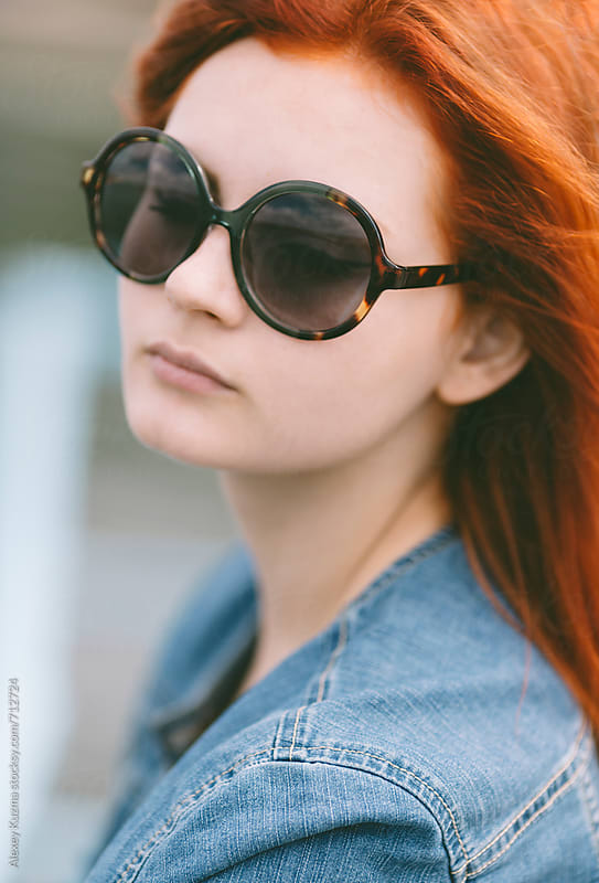 portrait of  young woman  with round retro sunglasses by Alexey Kuzma for Stocksy United