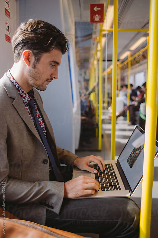 Young business man working in a train by Jovo Jovanovic for Stocksy United