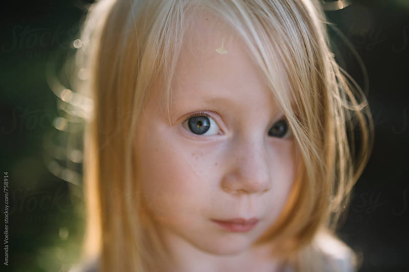 Innocent Close up Portrait of a little girl with blonde hair  by Amanda Voelker for Stocksy United