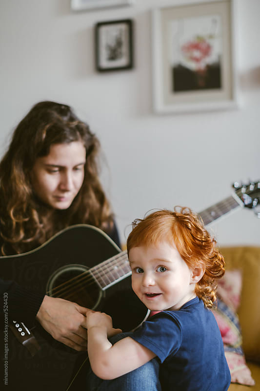 Mother Playing Guitar For Her Son by minamoto images for Stocksy United