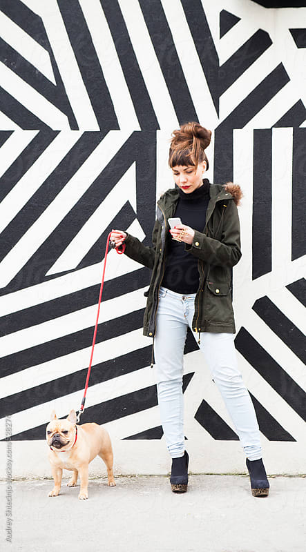 Young handsome woman with her pet typing text message on phone.  by Audrey Shtecinjo for Stocksy United