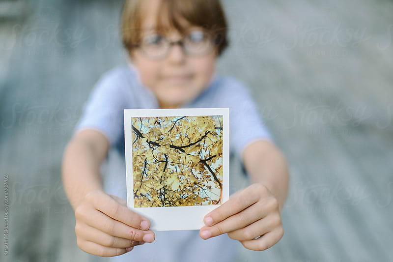 Boy holding an instant image of autumn leaves by Kirstin Mckee for Stocksy United