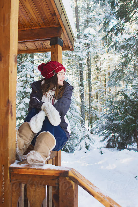 young woman sits on cabin porch in snowy mountains by Tana Teel for Stocksy United