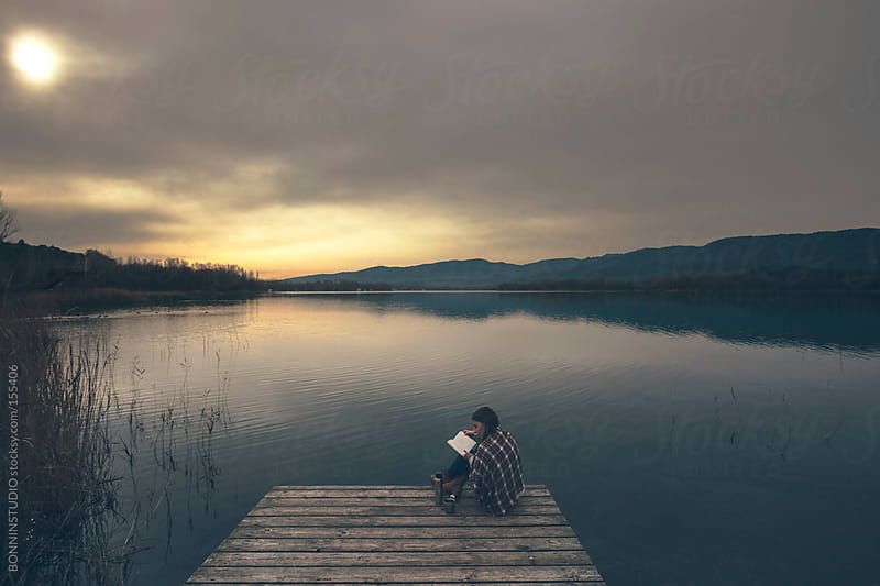 Young woman reading on beautiful views of the lake. by BONNINSTUDIO for Stocksy United