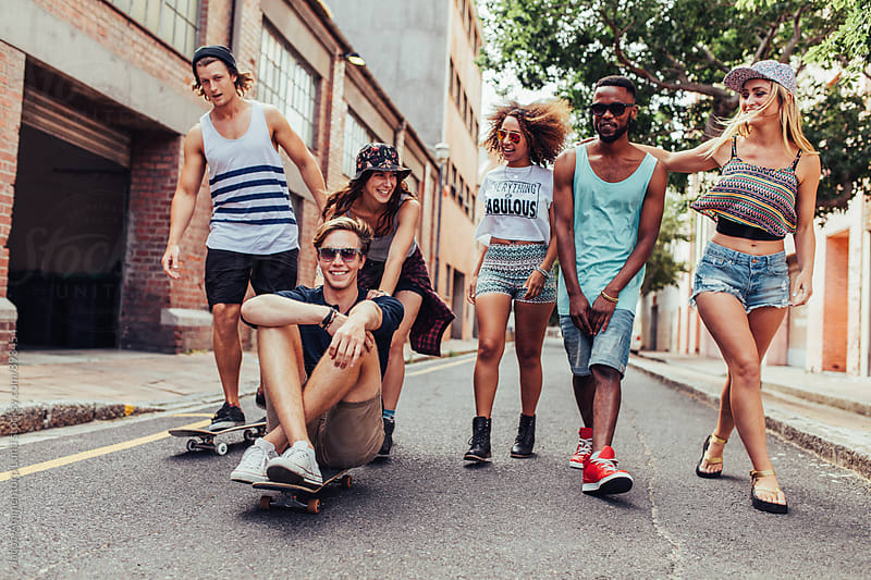 Group of mixed race young friends on the city street by Jacob Lund for Stocksy United