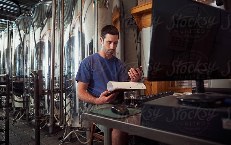 Beer: Brewer Checks Times Against Clipboard At Desk by Sean Locke for Stocksy United