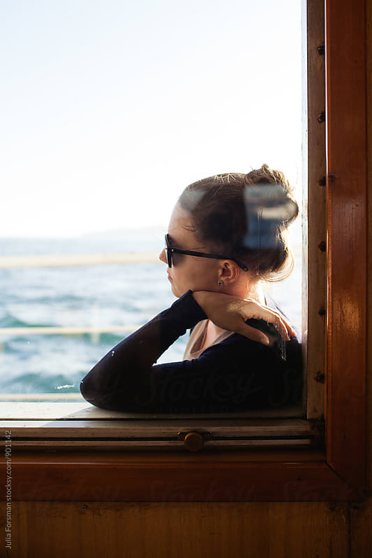 Young woman wearing sunglasses leans against the window of the ferryboat she is travelling on. by Julia Forsman for Stocksy United