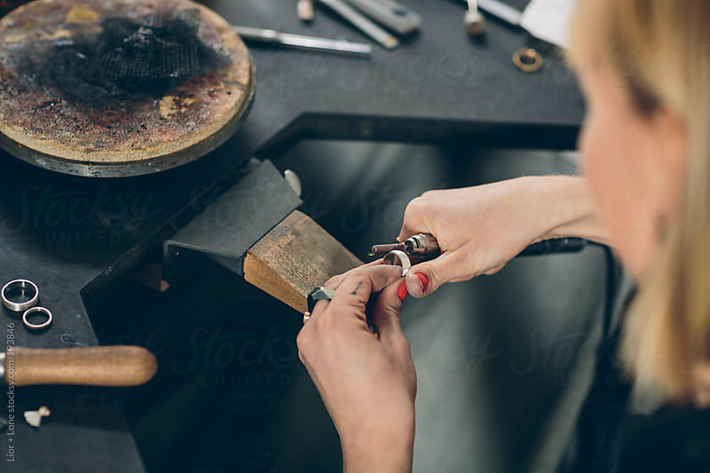 Closeup of a jewelry designer working on a new piece in her workshop by Lior + Lone for Stocksy United