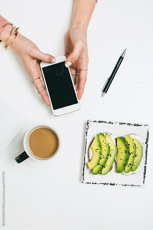 Woman's hands using her smartphone from above. by BONNINSTUDIO for Stocksy United