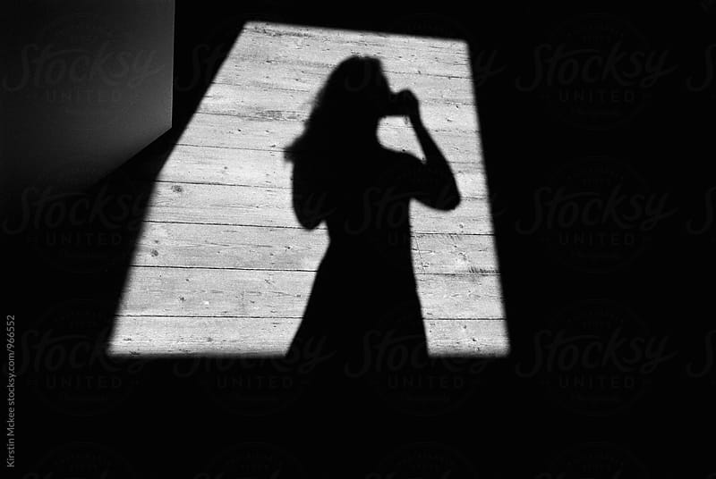 Shadow of woman in window of light by Kirstin Mckee for Stocksy United