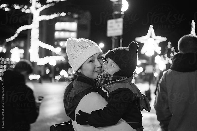 Black and white photo of mommy and child smiling, enjoying each other's company during the Holidays by Lawrence del Mundo for Stocksy United