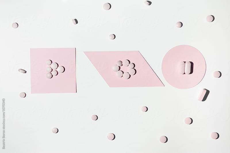 Pink pills in geometrical shapes by Beatrix Boros for Stocksy United