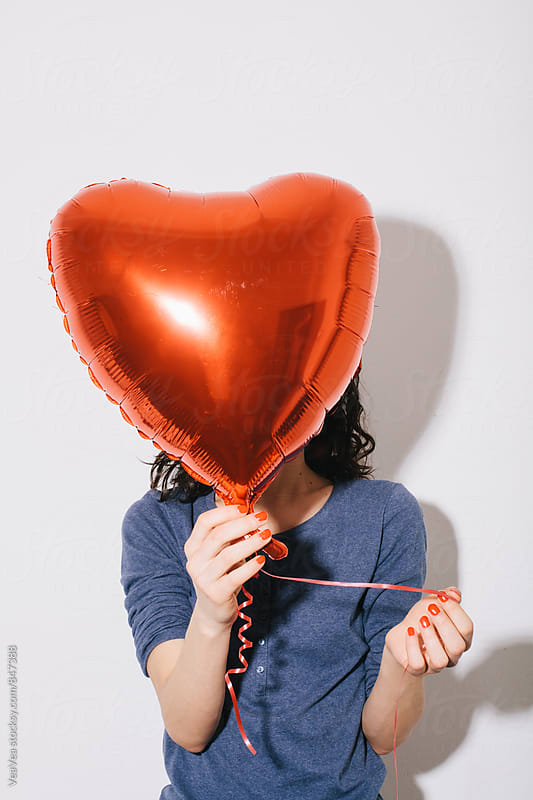 Woman holding a heart shaped balloon  by VeaVea for Stocksy United