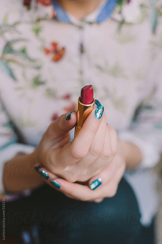 Woman Holding a Red Lipstick by Lumina for Stocksy United