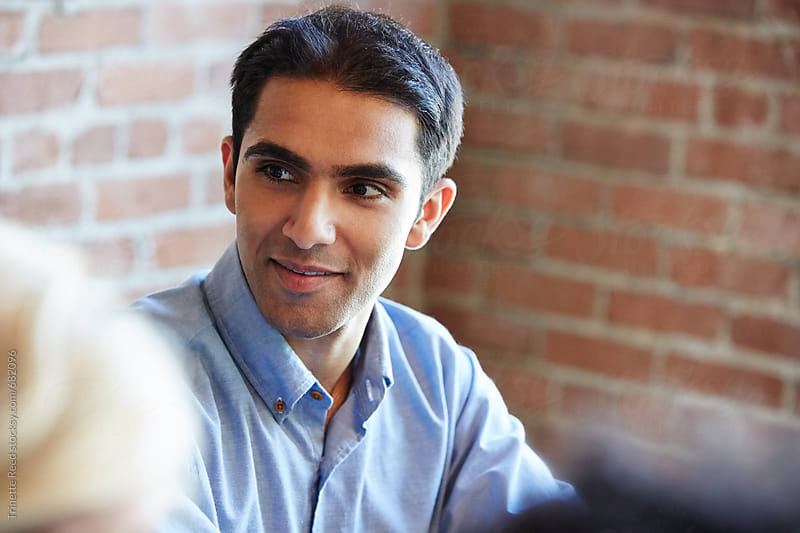 Close-up portrait of millennial Indian businessman in meeting by Trinette Reed for Stocksy United