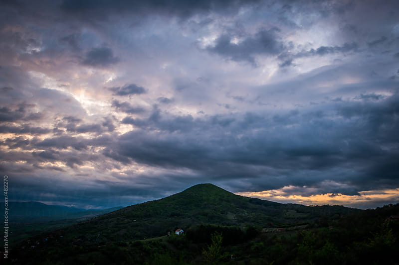 Dramatic clouds during sunset with hill in the middle by Martin Matej for Stocksy United