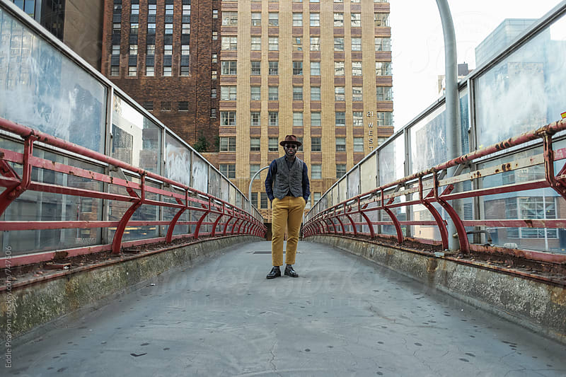 Stylish man standing in the middle of a bridge by Eddie Pearson for Stocksy United