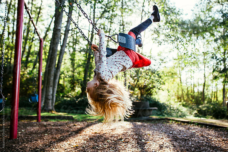 A Little Girl Swings Upside Down On the Swing by Amanda Voelker for Stocksy United