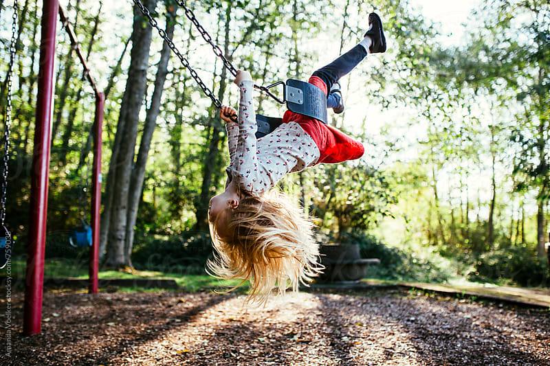 A Little Girl Swings Upside Down On the Swing by Amanda Voelker for Stocksy United