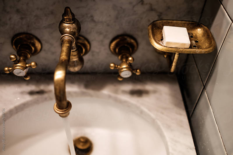 Soap in an antique brass soap dish next to a sink. by Riley Joseph for Stocksy United